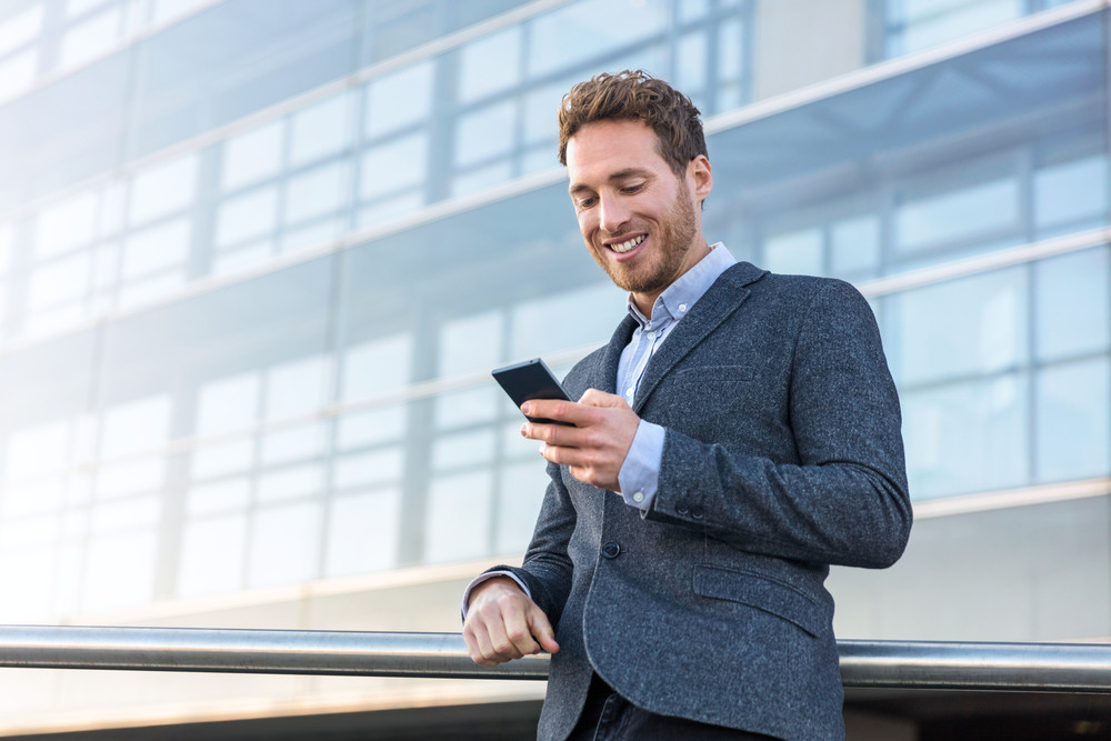 Businessman,Using,Mobile,Phone,App,Texting,Outside,Of,Office,In